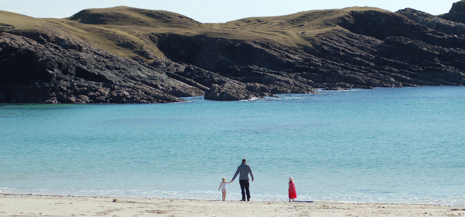 family walking on white sand of Clachtoll beach