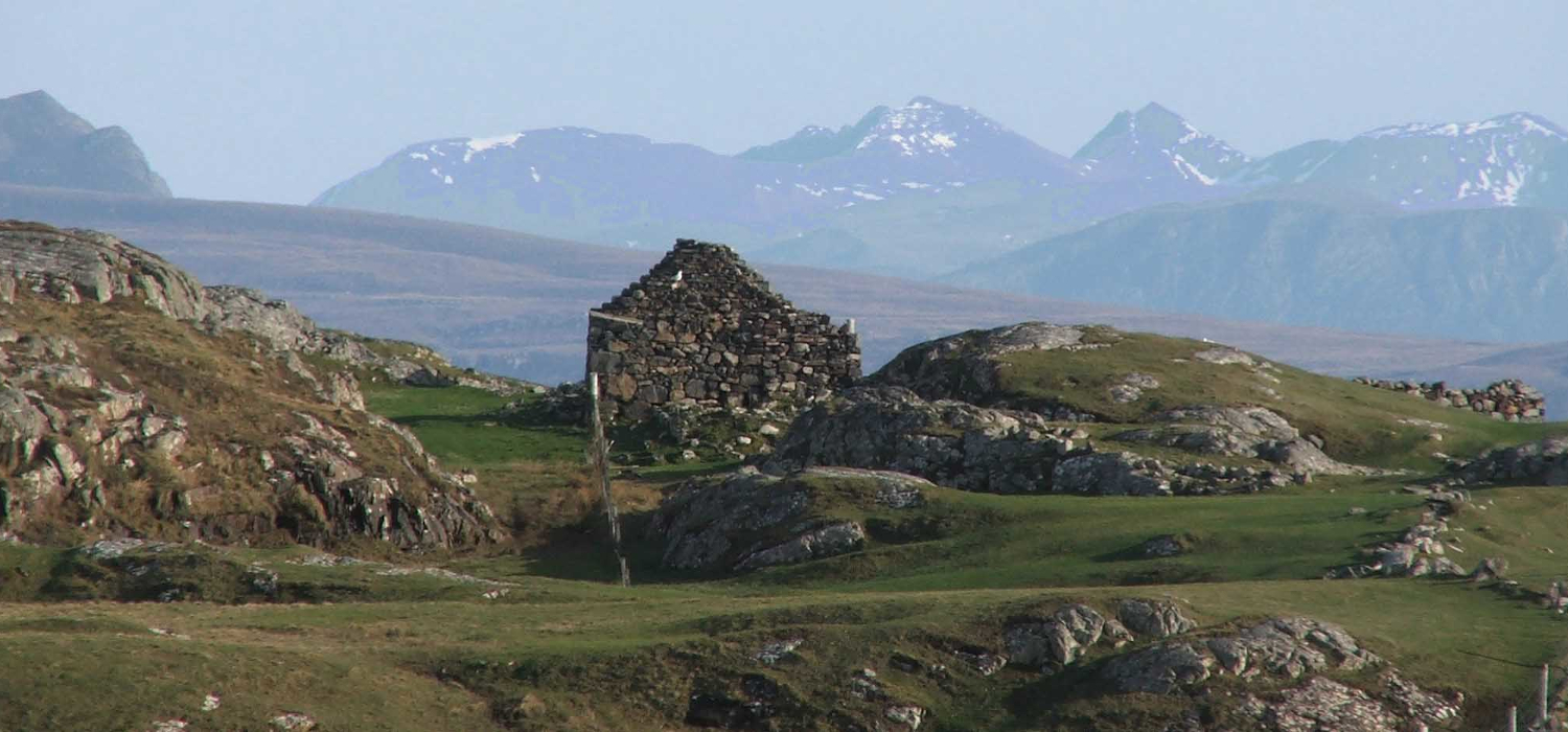 gable end of ruined cottage with mountains of Wester Ross behind