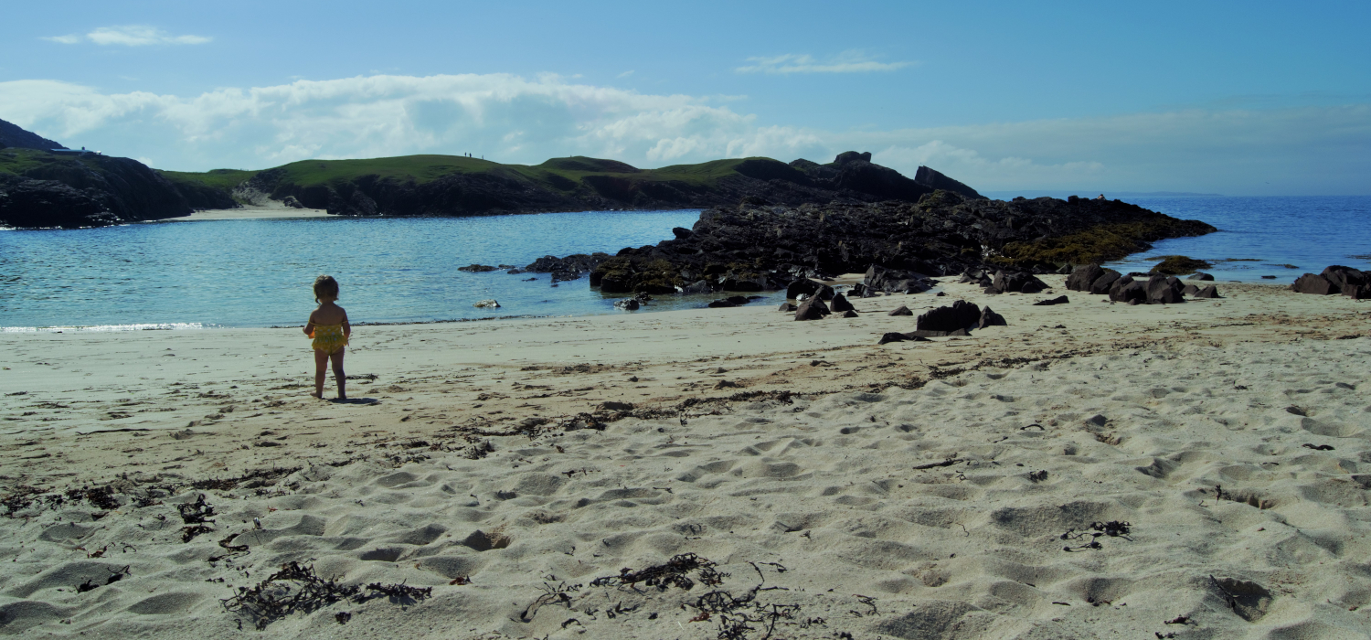 wee girl standing on Clachtoll beach in the sun